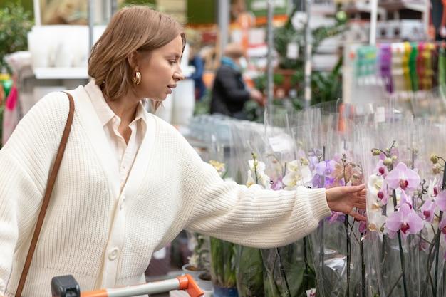 Frau mit einkaufswagen, die orchideenblumen für ihr haus im gewächshaus oder im gartencenter auswählt und kauft