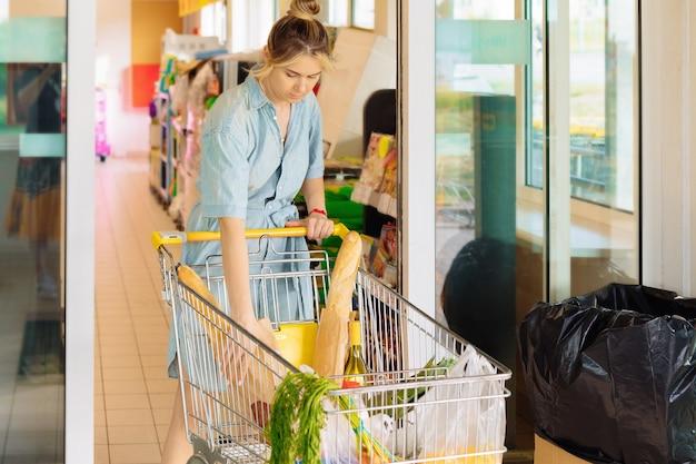 Frau mit einkaufswagen gefüllt mit lebensmitteln, die an einem sommertag in freizeitkleidung aus dem supermarkt kommen