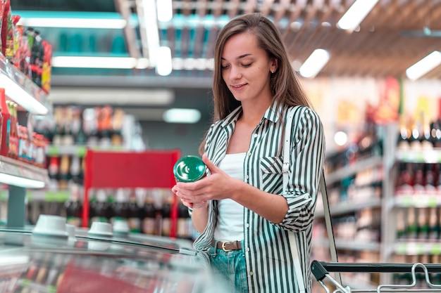 Frau mit einkaufswagen wählt, prüft produktetikett und kauft lebensmittel im lebensmittelgeschäft