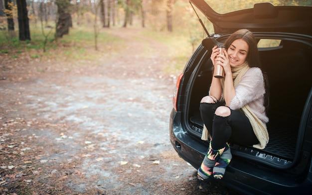 Frau mit einwegtasse kaffee neben dem auto. schließen sie die hand. herbst-konzept. herbstwaldfahrt mit dem auto.