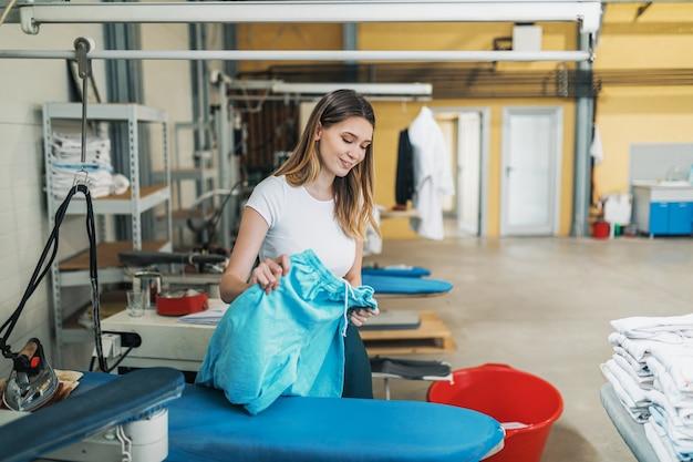 Frau mit eisen, die an der bügelwerkstatt arbeitet. reinigungsdienste.