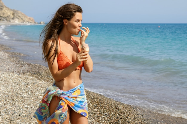 Frau mit eistüte am strand