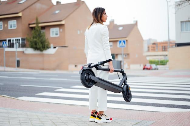 Frau mit elektroroller über die straße