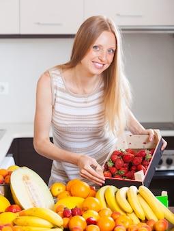 Frau mit erdbeeren und anderen früchten