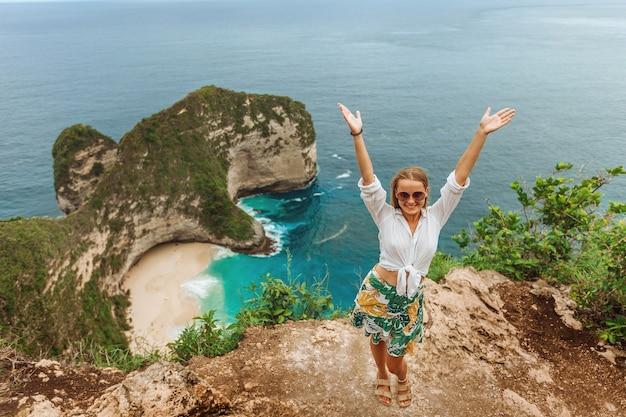 Frau mit erhobenen händen am kelingking beach auf nusa penida bali indonesia