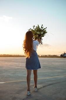 Frau mit erhobenen händen und lilienstrauß, der auf dem flugplatz steht. sonnenuntergang weiches licht.
