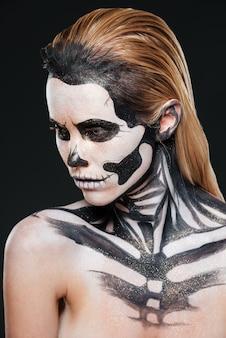 Frau mit erschreckend erschrockenem make-up auf schwarzem hintergrund