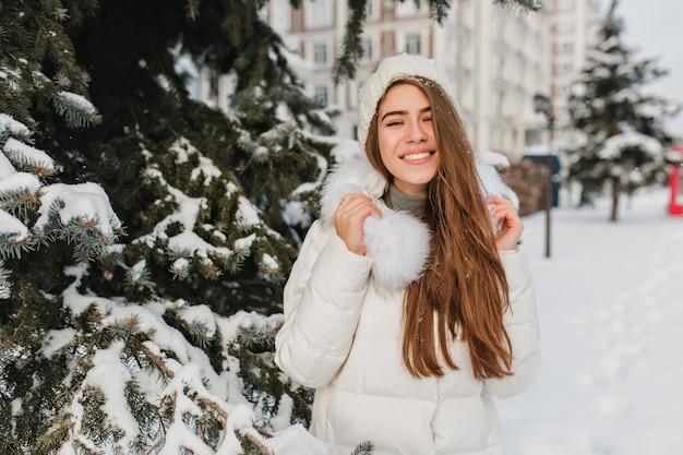 Frau mit erstaunlichem lächeln, das winterurlaub im park mit schneebedeckten bäumen verbringt. außenporträt der frohen europäischen frau mit den langen haaren, die frische luft am kalten tag genießen.