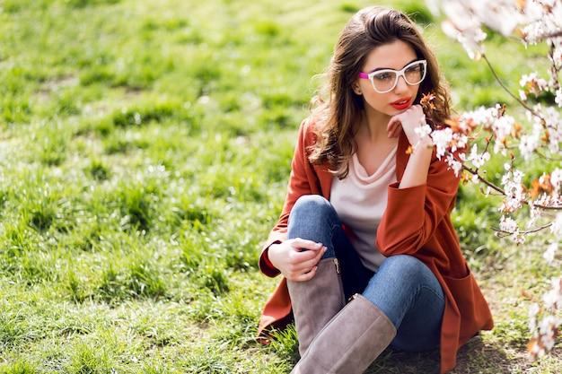 Frau mit erstaunlichen roten lippen, kühle brille auf dem gras tragend