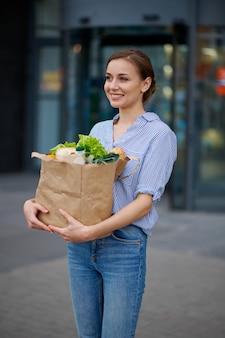 Frau mit essen im karton auf dem parkplatz des supermarkts. zufriedener kunde mit einkäufen in der nähe des einkaufszentrums, weibliche person, die obst und gemüse kauft buying