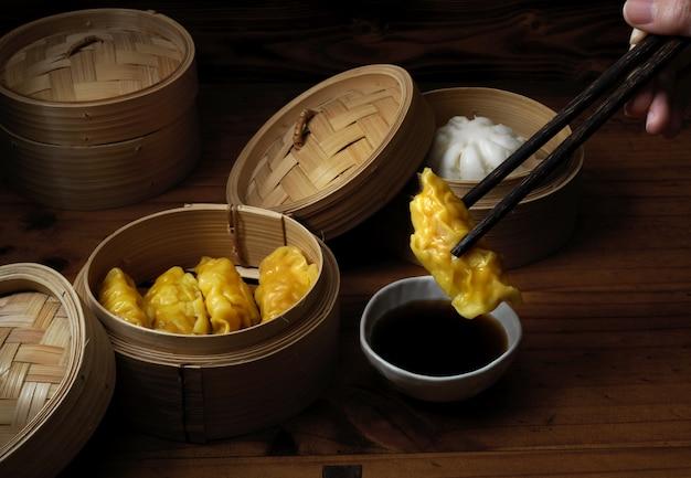 Frau mit essstäbchen bereit, gedämpfte knödel zu essen, die auf bambussitzer in chinesischen restaurants dienen