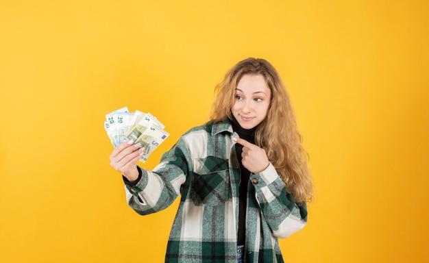 Frau mit euro-banknoten in der hand, die darauf zeigt, gelber hintergrund