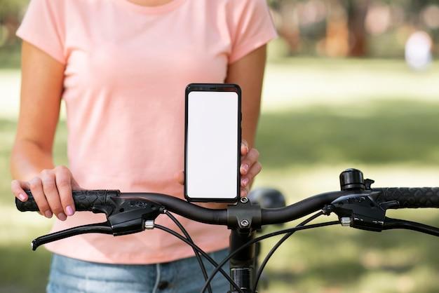 Frau mit fahrradkopieraum-mobiltelefon