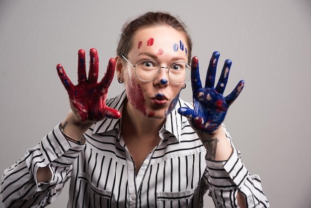 Frau mit farben auf ihrem gesicht und brille auf grauem hintergrund