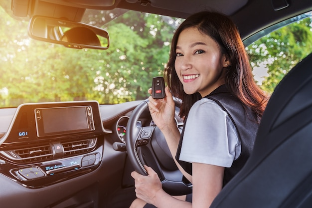 Frau mit fernbedienung des intelligenten schlüssels in einem auto