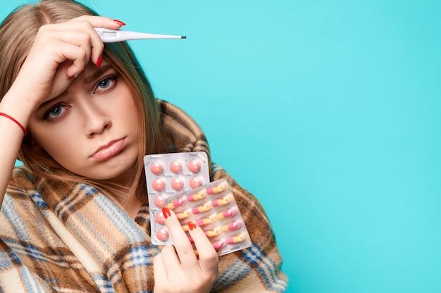 Frau mit fieber und einem thermometer in den händen trinkt pillen und wickelt sich in ein plaid