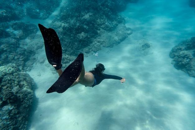 Frau mit flossen, die im ozean schwimmen