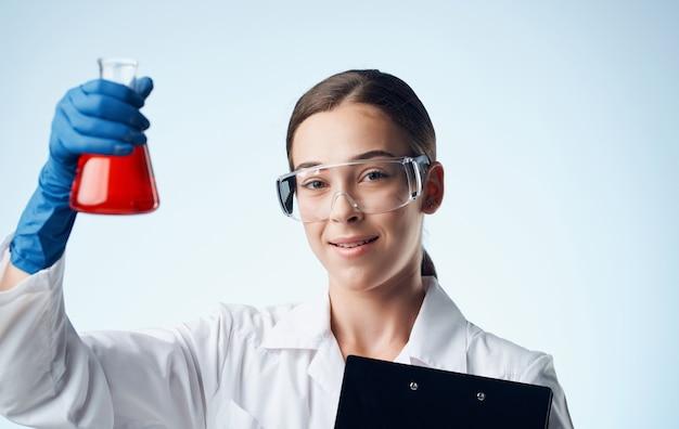 Frau mit flüssigkeit in einem kolbenlaborforschung chemisches element ordner mit dokumenten
