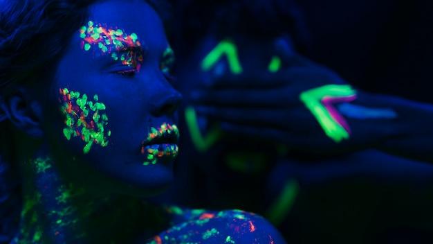Frau mit fluoreszierendem make-up auf gesicht und hand