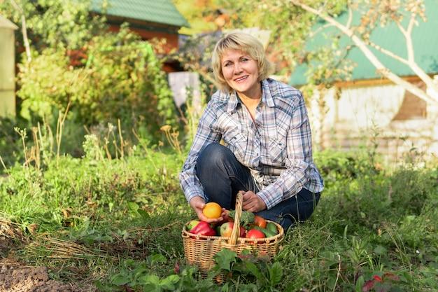 Frau mit frischem gemüse in einem korb im garten im herbst