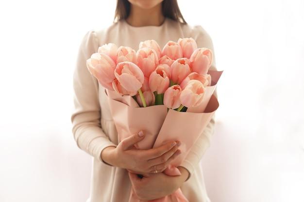 Frau mit frühlingsblumenstrauß. glückliche überraschte vorbildliche frau, die blumen riecht. muttertag. frauentag. frühlingsblumenzusammensetzung.
