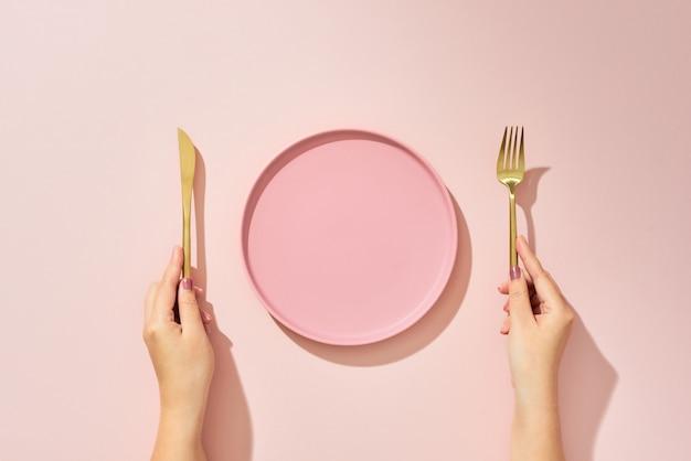 Frau mit gabel, messer und leerem teller auf rosa draufsicht