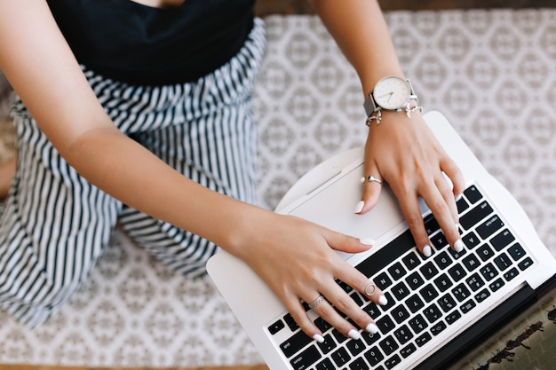 Frau mit gebräunter haut, die auf tastatur tippt, während sie auf ihren knien steht