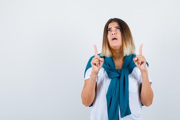 Frau mit gebundenem pullover, der nach oben zeigt, im weißen t-shirt nach oben schaut und hoffnungsvoll aussieht, vorderansicht.