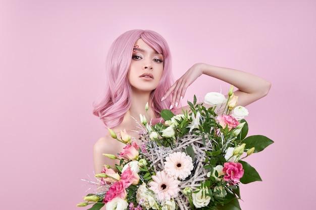 Frau mit gefärbtem rosa starkem haar hält einen strauß schöner blumen in ihren händen. natürlich gefärbtes haar schönes make-up