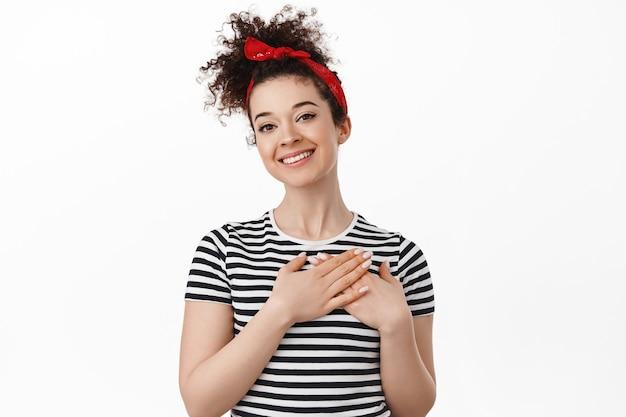 Frau mit gekämmten lockigen haaren, stirnband, händchen am herzen haltend und dankbar aussehend, dankend, berührt oder geschmeichelt, über weiß stehend