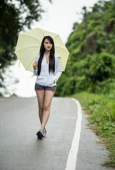 Frau mit gelbem regenschirm allein als regnen