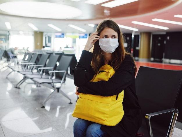 Frau mit gelbem rucksack, die am flughafen wartet, wartet verspätung