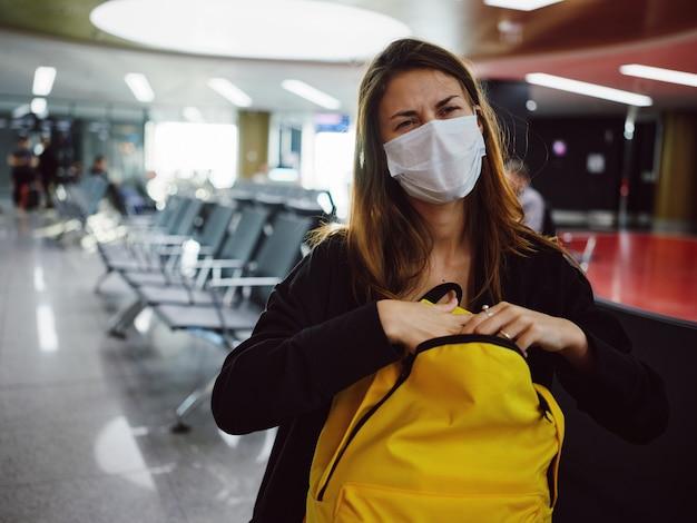 Frau mit gelbem rucksack sitzt am flughafen und wartet auf unzufriedenheit