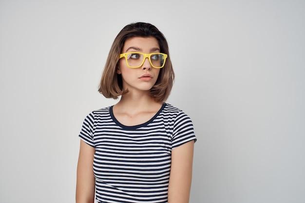 Frau mit gelber brille gestreiftes t-shirt beschnittenen hellen hintergrund. foto in hoher qualität
