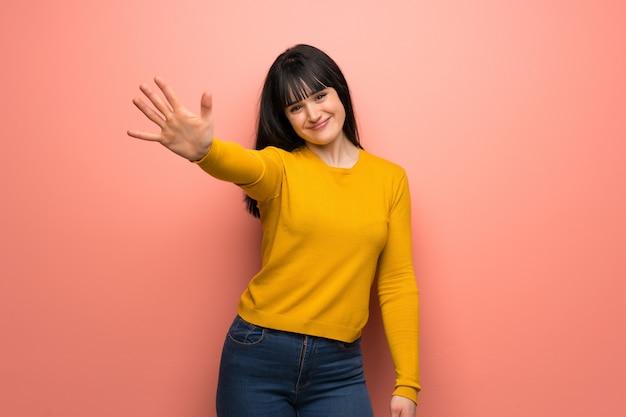 Frau mit gelber strickjacke über der rosa wand, die fünf mit den fingern zählt