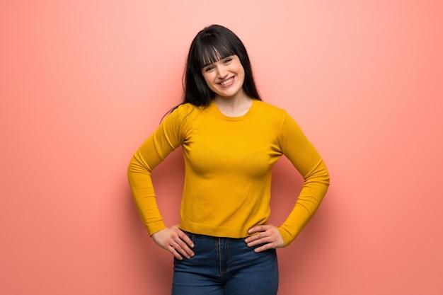 Frau mit gelber strickjacke über der rosa wand, die mit den armen an der hüfte und am lächeln aufwirft