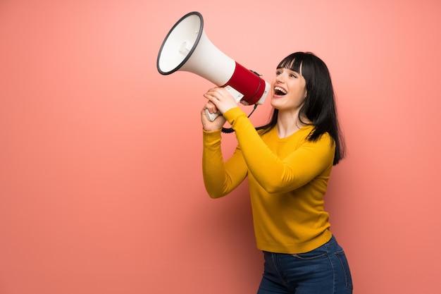 Frau mit gelber strickjacke über rosa wand schreiend durch ein megaphon