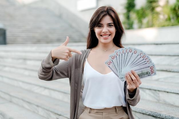 Frau mit geld draußen in der stadt