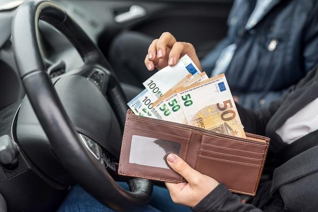Frau mit geldbörse mit euro im auto sitzend