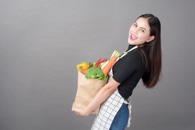 Frau mit gemüse in einkaufstüte