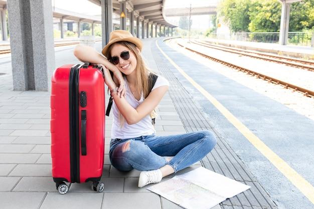 Frau mit gepäck beim sitzen auf dem boden