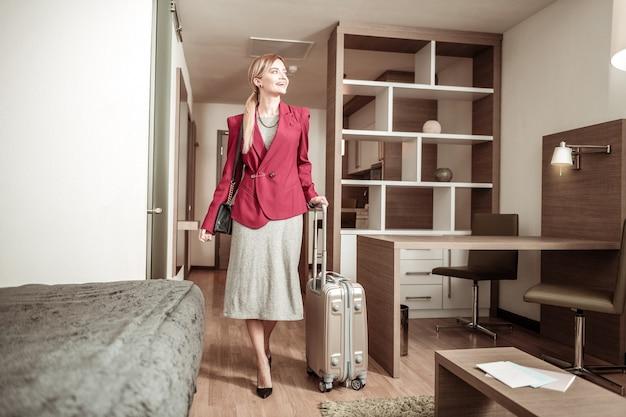 Frau mit gepäck. blondhaarige stilvolle junge frau, die mit ihrem gepäck zum hotelzimmer kommt