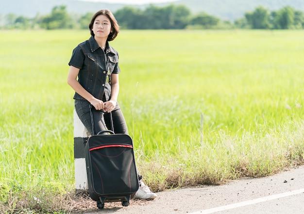 Frau mit gepäck per anhalter entlang einer straße