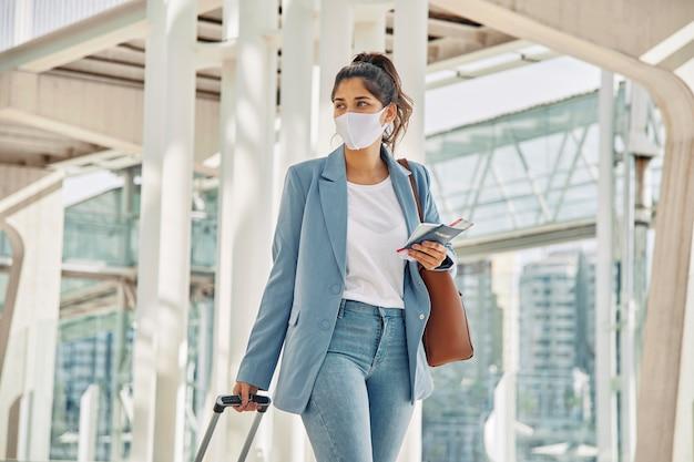 Frau mit gepäck und medizinischer maske am flughafen während der pandemie