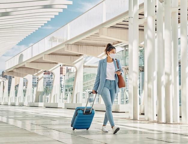 Frau mit gepäck während der pandemie am flughafen