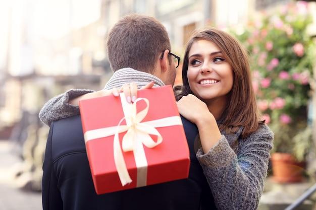 Frau mit geschenk umarmt ihren mann