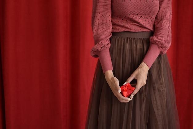 Frau mit geschenkbox auf rotem grund