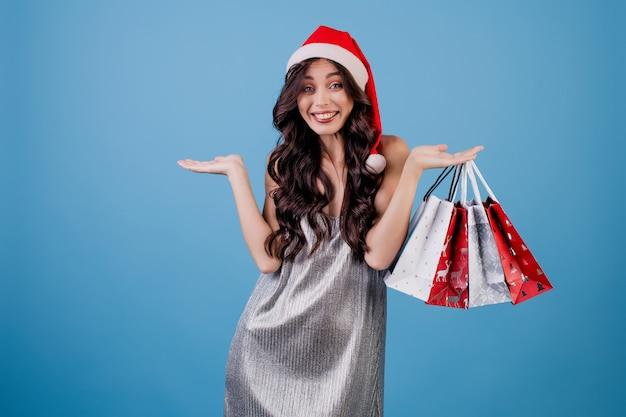 Frau mit geschenken in den einkaufstaschen, die sankt-hut tragen