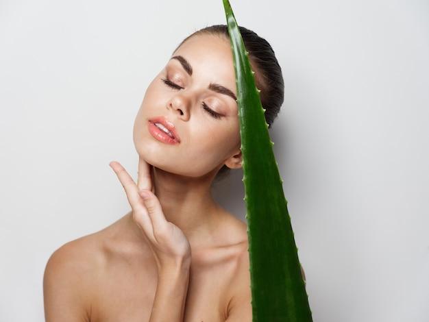 Frau mit geschlossenen augen, die aloe-blatt in der hand hält, saubere hautkosmetik. foto in hoher qualität