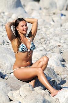 Frau mit geschlossenen augen, erhobenen armen und nahem kopf, im badeanzug, der auf steinen an der küste sitzt